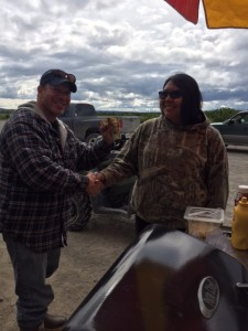 Villager Karl Hill makes the first transaction on opening day of the food stand.