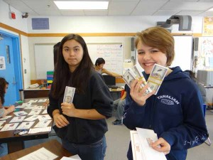 Students flash their play money at the $pending Frenzy workshop.