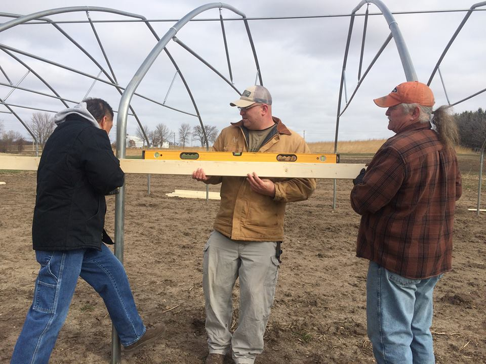Darwin Summer, Eugene Standing Cloud and Michael Van Horn of Gitagaanike (RLLFI) work together to construct a high tunnel during a training at Wozupi Tribal Gardens in Prior Lake, Minnesota, in March 2016.