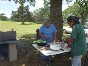 Outdoor cooking demonstrators Sue Givens and Veronica Givens prepare recipes with food items from the FDPIR traditional foods basket for the Seminole Nation's Food and Nutrition program.