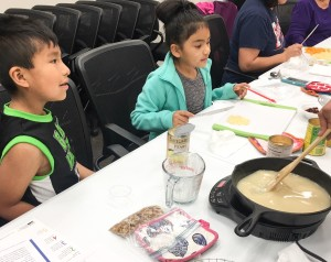 Seminole Nation youth, Leland age 7 and Isabella age 8, learn how to prepare a skillet peach cobbler as part of the Seminole Nation's Food and Nutrition program at the Cvfekne Wellness Center.