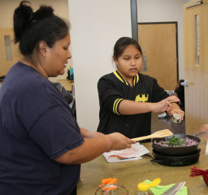 Lenore Johnson and her daughter Briana, age 12, prepare citrus salmon, using food items from the FDPIR traditional foods basket as part of the Seminole Nation's Food and Nutrition program at the Cvfekne Wellness Center.