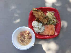 Salmon filet and chicken cooked in a cast-iron skillet along with rice, cabbage and hominy with pork. All the recipes were cooked over an open wood flame outdoors by the Seminole Nation's Food and Nutrition program using food items from the FDPIR traditional foods basket and FDPIR foods.