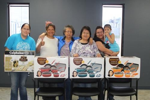 (Left to right) Robin Green, Angie Longie, Pam Rainbow, Marcella Green, Eunice Green and her daughter Jazmyn show off new bakeware and cookware they received after completing the Nutrition Mission Lessons as part of the Spirit Lake Nutrition Passport program.