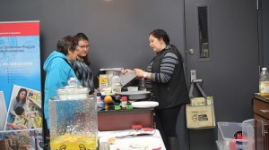 Elisha Poulsen, Spirit Lake FDPIR Nutrition Educator, shows participants Marcella Green and Eunice Green how to prepare a stir fry recipe as part of the Spirit Lake Nutrition Passport program.