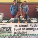 "Ho-Chunk food sovereignty assessment kickoff ""movie night,"" with Melanie Stacy (seated) and standing (left to right) Jessika Greendeer and Danielle Hill with baby Maple"