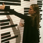 "Chandra interacts with the ""Kill the Indian, Save the Man"" exhibit, in which black bars turn translucent when touched and reveal the names of U.S. Indian Boarding Schools that have been lost to history. Chandra has her hand on the boarding school Carlisle, where her great grandmother Elizabeth Bender and great uncle Charles Bender were sent."