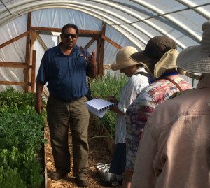 George Toya describes the greenhouse operation at Nambé Pueblo, while Wendy, a Master Gardener (closest to George), listens and takes notes.
