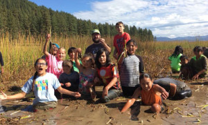 Salish immersion upper elementary class (grades 3-6) harvesting wapatos in Calispel Lake. Wapatos are an aquatic bulb and traditional food source.