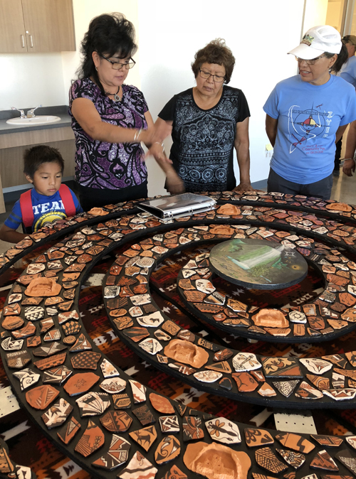 A focal point of the community center is the showcase of pottery shards, each decorated with images and designs of Zuni culture. The table creates a display that visitors can walk around and experience.