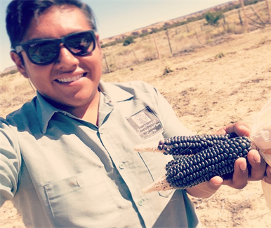 Aaron Lowden, Acoma Ancestral Lands Program Coordinator, holding dryland blue corn.