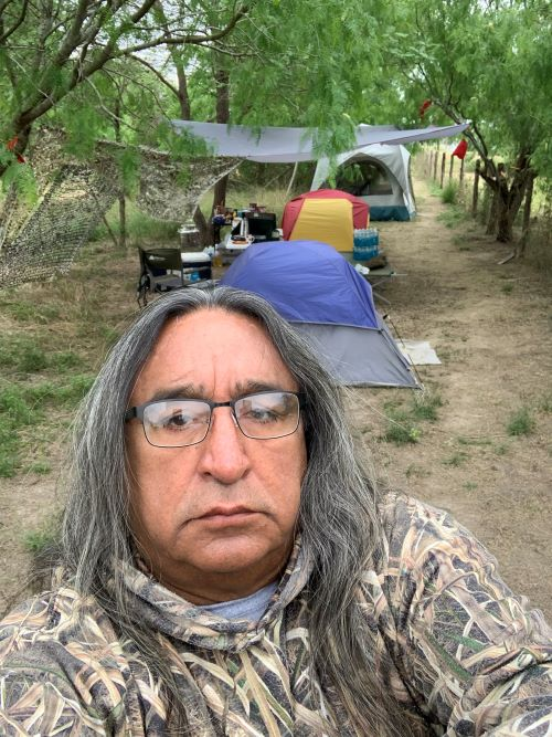 Juan Mancias stands before Mariposa Village, one of the three camps in South Texas. Funds for Project Stop Texas LNG will go toward replenishing these camps with supplies, food, water, gas, and video and monitoring equipment.
